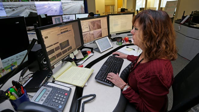 Control room operator Melanie Pape works on placing messages on the overhead highway electronic message boards at the Statewide Traffic Operations Center at the Milwaukee Intermodal Amtrak station. The Wisconsin DOT is partnering with the popular crowd-sourced traffic app Waze to share real-time traffic information for motorists.