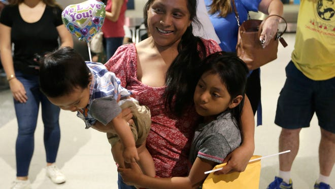 Buena Ventura Martin-Godinez, center, holds her son Pedro, left, as she is reunited with her daughter Janne, right, at Miami International Airport on July 1, 2018, in Miami. Martin crossed the border into the United States from Mexico in May with her son, fleeing violence in Guatemala. Her husband crossed two weeks later with their 7-year-old daughter Janne. All were caught by the Border Patrol, and were separated. Her daughter was released Sunday from a child welfare agency in Michigan.