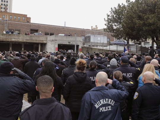 Hundreds of police officers fill in the back entrance to the Medical Examiner's office and salute while the casket is moved from the hearse in Milwaukee on Wednesday, Feb. 6, 2019.