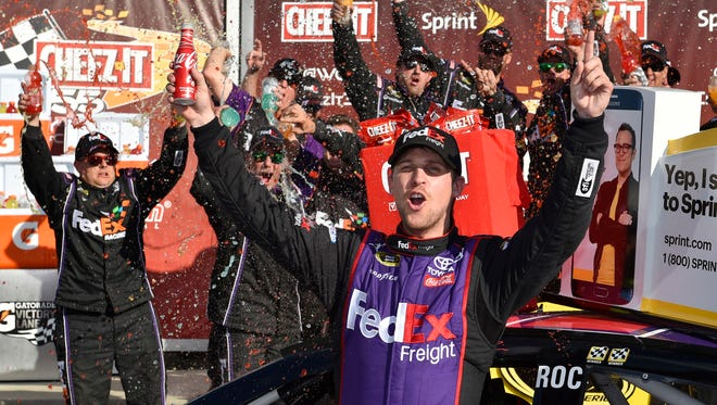 Denny Hamlin celebrates in Victory Lane after winning a NASCAR Sprint Cup Series auto race at Watkins Glen International, Sunday, Aug. 7, 2016, in Watkins Glen.