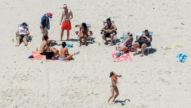 Gov. Chris Christie, right, uses the beach with his family and friends at the governor's summer house at Island Beach State Park on Sunday. Christie is defending his use of the beach, closed to the public during New Jersey's government shutdown.