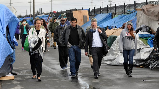 City councilmember Jose Casta–eda, in black, and lawyer Anthony Prince walk through Chinatown on Tuesday on their way to present a lawsuit on behalf of the homeless to the office of the Salinas city attorney.