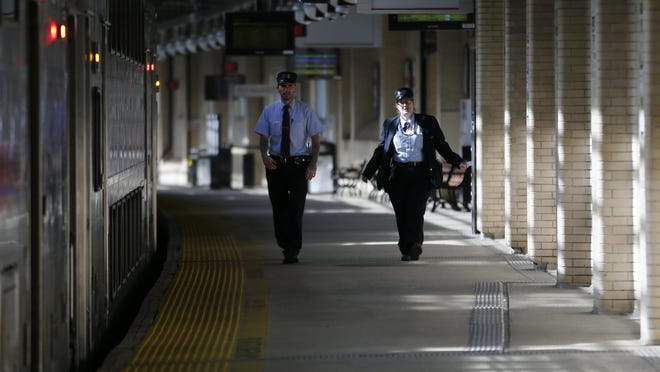 NJ Transit employees walk on the platform at Newark Penn Station, Friday, March 11, 2016, in Newark, N.J. New Jersey Transit and its rail workers reached a deal Friday to avert a strike that would have thrown Monday's commute into New York into chaos. (AP Photo/Julio Cortez)