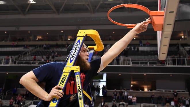 Gonzaga Bulldogs center Przemek Karnowski climbs the ladder to cut down the net.