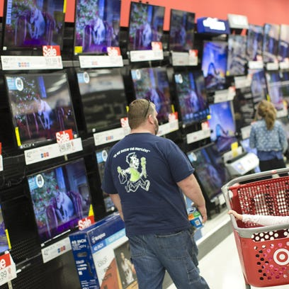A child rests in a shopping cart in the electronics section against a backdrop of televisions at a Target store on Friday in Newport, Ky.
