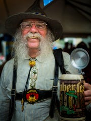 Stewart Eastman of Abita Springs, La. waits under a tent to avoid the rain at Oktoberfest Friday, September 16, 2016 in downtown Zinzinnati before Oktoberfest.