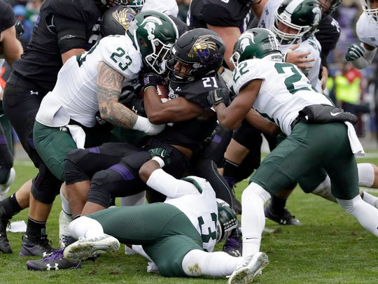 Northwestern running back Justin Jackson (21) is tackled
