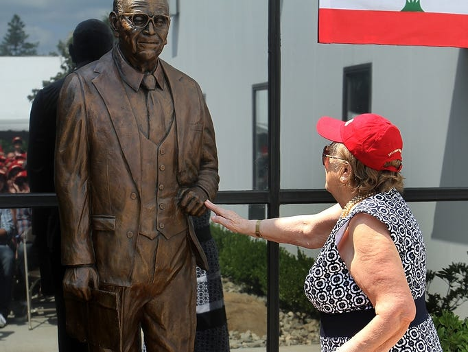 Nada Sauma, widow of IAS Corporation founder Yussef Sauma, touches a statue of her late husband during the company's Summer Celebration, Sunday, August 17, 2014, in Piscataway, NJ. Photo by Jason Towlen