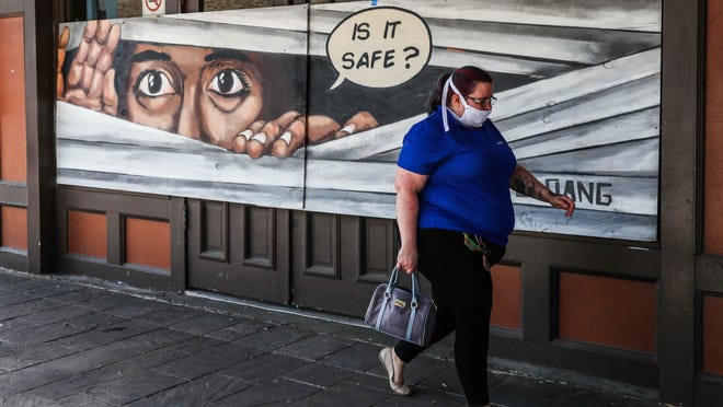 Andrea Jansen walks in front of a mural on 6th Street wearing a mask amid coronavirus pandemic as Gov. Greg Abbott address Reopening of Texas Economy in Austin on Monday, April 27, 2020.