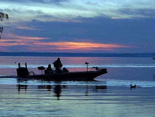 An angler motors across Toledo Bend at sunset. The
