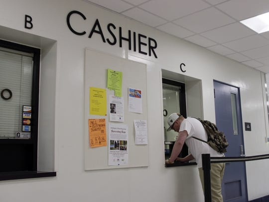 A College of the Sequoias student pays fees at the Visalia campus cashier office on Tuesday morning.