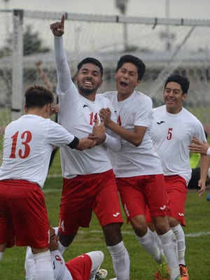 Hueneme's Diego Caballero (14) points to the stands after scoring the first goal of a 3-0 win over Pacific View League co-leaders Pacifica on Friday afternoon. Teammates Erik Lopez (13), from left, Esteban Mora (4) and Andres Viera (5) enjoy the celebration.