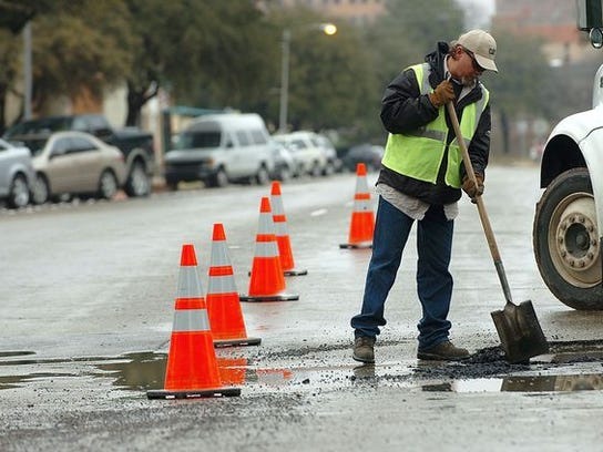A city of Abilene street services worker fills a pothole at the intersection of South 4th and Chestnut streets on Feb. 4, 2010.