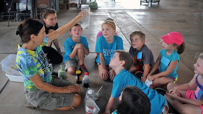 In this file photo, River Bend Nature Center education coordinator Leslie Fernandez, left, shows campers how different liquids separate themselves based on their density. The center offers a variety of summer camp options.