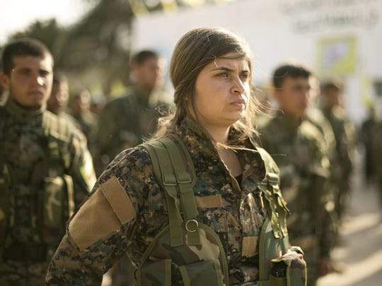 U.S.-backed Syrian Democratic Forces (SDF) stand in formation at a ceremony to mark their defeat of Islamic State militants in Baghouz, at al-Omar Oil Field base, Syria, Saturday, March 23, 2019.