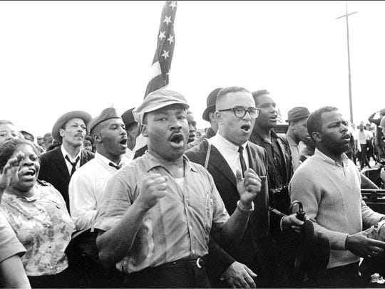 Dr. Martin Luther King Jr. leads singing marchers from