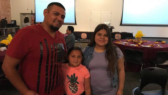 Antonio Diaz, 29, is pictured with his two daughters at his GED graduation ceremony on Thursday.