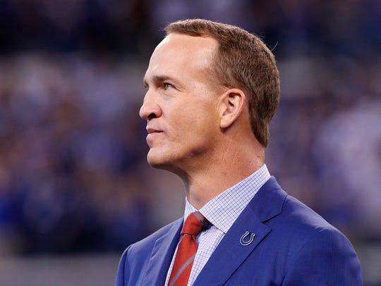 Former Colts quarterback Peyton Manning watches a video
