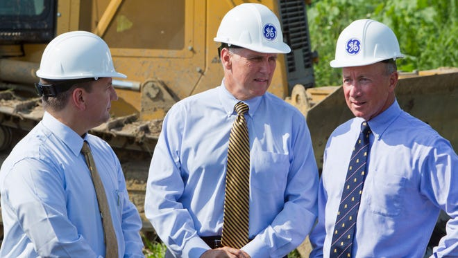 General Electric Vice President Tony Aiello, left, Indiana Governor Mike Pence and Purdue President Mitch Daniels talk after breaking ground for a General Electric Aviation facility Monday, July 21, 2014, in Lafayette. The plant will build  GE's LEAP jet engine, a high-efficiency aircraft engine . The plant is expected to employ 200 people.