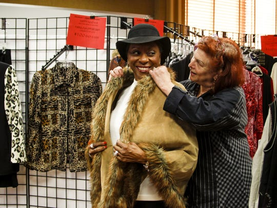 Madeline Flaster, right, co-founder of the Jacobson's Alumni Association, helps fit Joann Doby, of Lansing, into a wrap on Dec. 6, 2015, during the Holiday Fashion Boutique clothing drive benefitting the Women's Center of Greater Lansing. Donors, like Doby, recieved coupons to buy new items from the Jacobson's Alumni Association boutique.