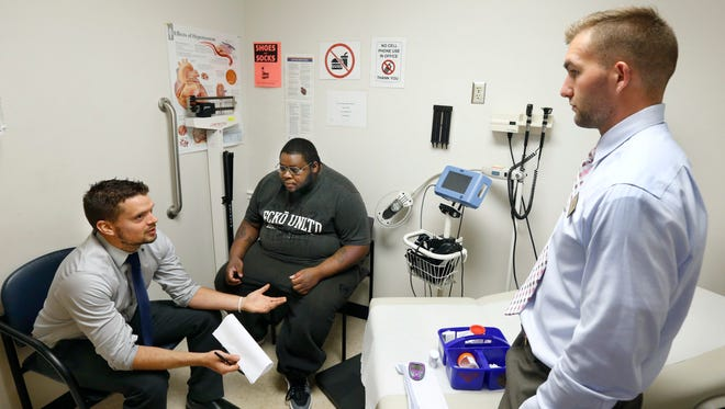 Clinical pharmacist Shawn Fellows of Livonia, next to patient Louis Young of Rochester, has a conversation with Luke Sanna of Fairport, a resident and student from St. John Fisher College's Wegmans School of Pharmacy, as he gets clinical training at the at Brown Square Health Center.