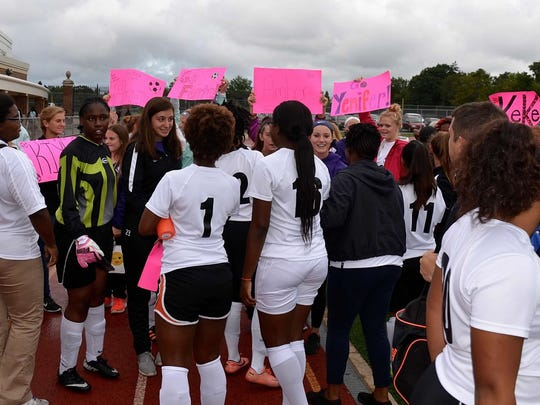 The Withrow girls varsity team receives signs of encouragement from their Glen Este counterparts.