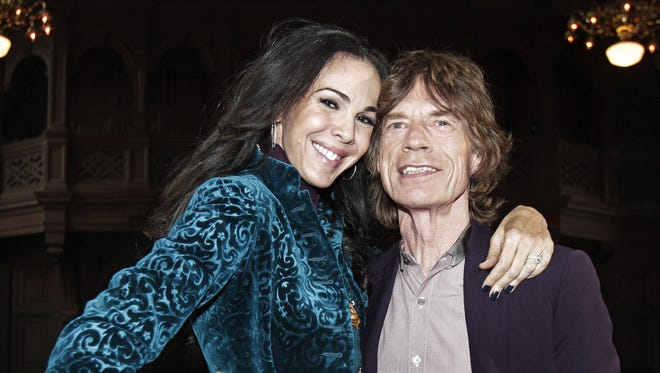 FILE - This Feb. 16, 2012 file photo shows singer Mick Jagger, right, with designer L?Wren Scott after her Fall 2012 collection was modeled during Fashion Week, in New York. Scott, a fashion designer, was found dead Monday, March 17, 2014, in Manhattan of a possible suicide. (AP Photo/Richard Drew, File)