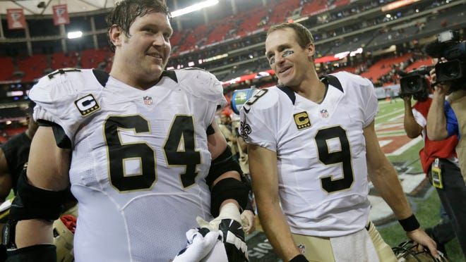 FILE - In this Jan. 3, 2016, file photo, New Orleans Saints quarterback Drew Brees (9) walks off the field with New Orleans Saints tackle Zach Strief (64) after the second half of an NFL football game against the Atlanta Falcons, in Atlanta. Strief says he's retiring after 12 NFL seasons. Strief, who made a tearful announcement on Monday, March 12, 2018, in Metairie, La., says his career far exceeded his expectations.  (AP Photo/David Goldman, File) ORG XMIT: NY167