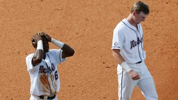 Ole Miss' Errol Robinson, left, and Will Golsan, right, walk off the field after losing to Texas A&M in a Southeastern Conference NCAA college baseball tournament game at the Hoover Met on Saturday.