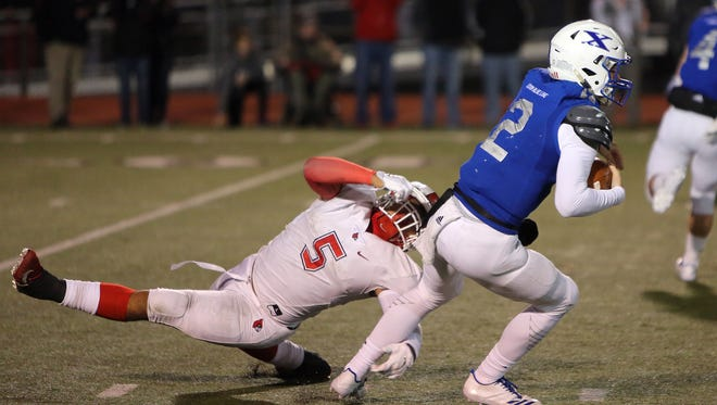 Saint Xavier quarterback Chase Wolf is brought down by Colerain linebacker Ivan Pace Jr. in the Division 1 Football Regional Finals at Mason High School in Mason Ohio.