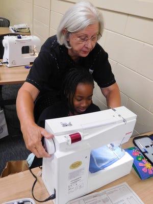 Susan Kirkland assists a camper making a garment.