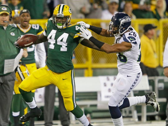 Green Bay Packers running back James Starks (44) fights off cornerback Cary Williams (26) against the Seattle Seahawks at Lambeau Field.