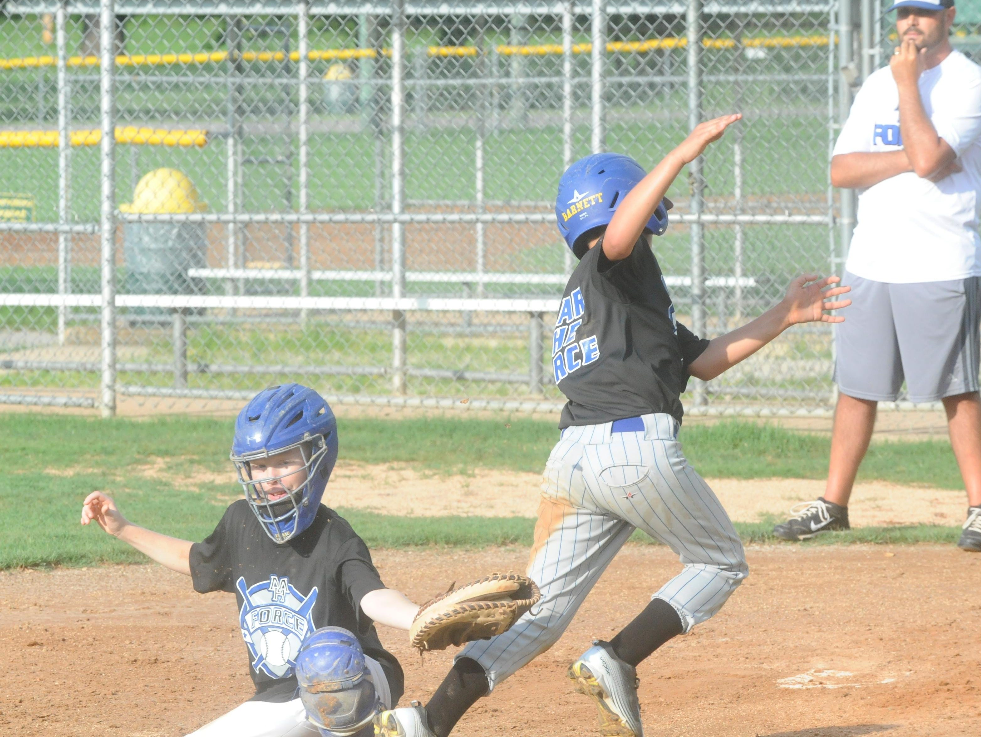 Mountain Home Force catcher Cody Lance, left, attempts to tag teammate Brady Barnett in a recent practice at Clysta Willett Park. The 10-year-old all-star team will play at the Cal Ripken World Series on Aug. 8-15 in Jonesboro.