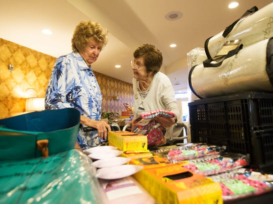 Gulf Coast Village residents, Ruth Cable, 98, right, and Marie Day peruse for sale items at a gift sale at the complex in Cape Coral.  Cable and Day are table mates.