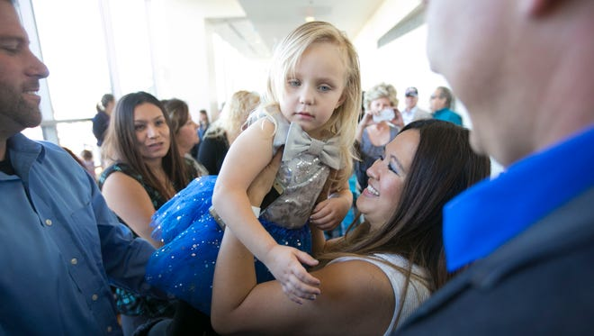 Cynthia Moynihan of Peoria, holds her about to be adopted daughter, Lily Moynihan, 3, before the court proceedings to make the adoption official during the 16th annual National Adoption Day at the Durango Juvenile Court building in Phoenix on Saturday, November 21, 2015. The Maricopa County Superior Court was expected to finalize 298 adoptions on National Adoption Day.