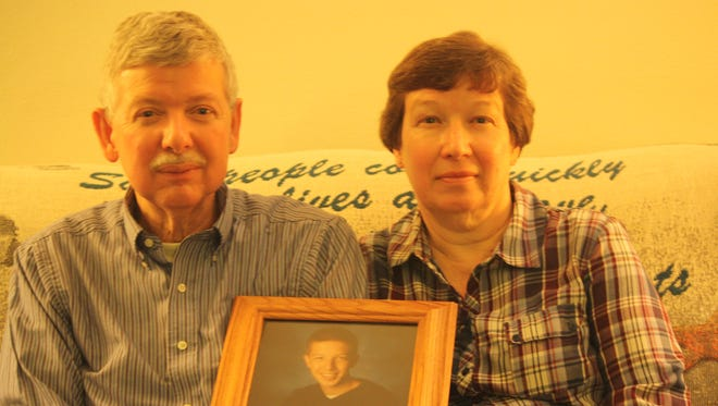 Doug and Jean Cox  hold a picture of their son, Steve Cox, in their Germantown home. Steve Cox, who was in high school in the photo, died after turning 30 in a crash at Kentucky Speedway.