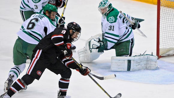 St. Cloud State's Joey Benik tries to get control of the puck against North Dakota's Paul LaDue (6) and goaltender Zane McIntyre during the first period of the Nov. 21 game at the Herb Brooks National Hockey Center in St. Cloud.