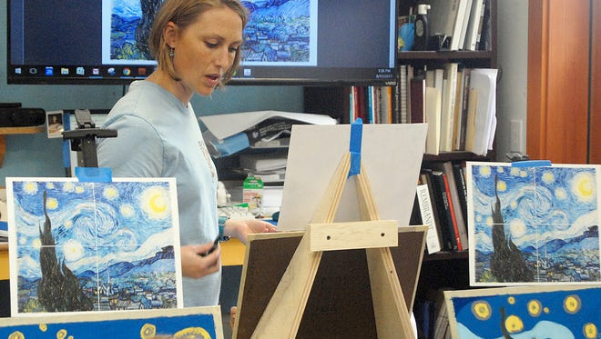 Mardie Rees brings her years of art education and experience to the classroom and talks of form and flow and compositional elements with a young student during a summer art class.