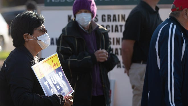 Some supporters of GOP candidates wear masks and hold signs during a bus tour stop in downtown Topeka. [2020 file photo/The Capital-Journal]