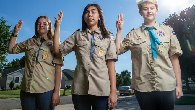 From left, Anna Newcome, Savannah Mazas and Camryn Clark give a 'Scout's Honor' outside of Clark's home Thursday afternoon. The girls are members of Boy Scout Troop 7 in Topeka.