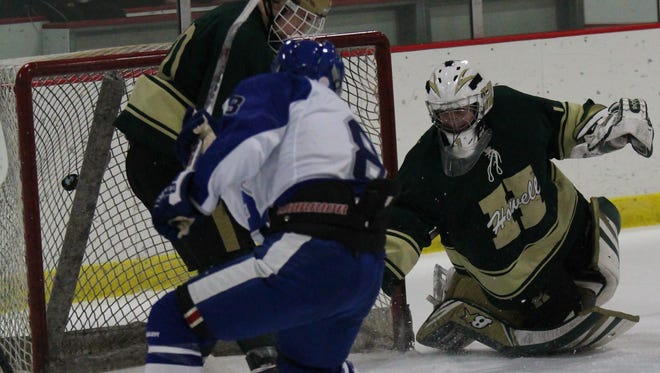 Scoring a goal in his first game of the season is Salem senior forward Richie Corso (No. 8), beating Howell netminder Nate George on the play. Corso required knee surgery over the summer.