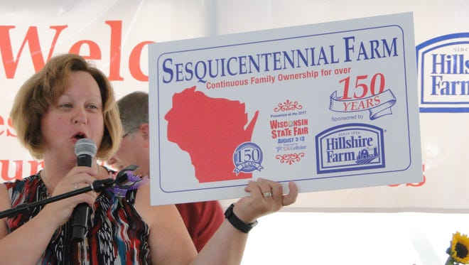 Jyme Buttke, Executive Secretary of Wisconsin Association of Fairs held up the sign the Sesquicentennial Farm families would be receiving at the conclusion of the special breakfast in their honor at Wisconsin State Fair. Century Farm families also received signs.