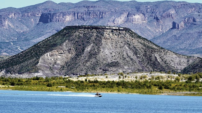 A lake visitor zips across Elephant Butte Lake on a recreational craft.
