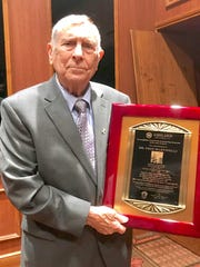 Former Ashland University football coach and College Football Hall of Fame inductee Fred Martinelli with the plaque he was presented as guest of honor at Thursday's fund-raising banquet for Team Focus.