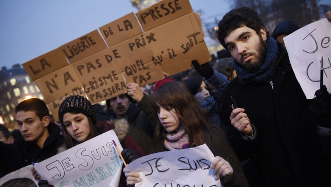 "A man holds a placard reading: ""Freedom of the press is priceless, fundamentalism, of any kind, will not pass"" as others hold up pens and placards reading in French, ""I am Charlie"" during a gathering at the Place de la Republique  in Paris on Jan. 7, 2015, following an attack by gunmen on the offices of the satirical weekly, ""Charlie Hebdo."""