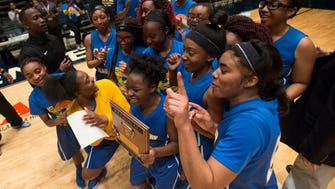 B.T. Washington's Jada Davison holds the Regional trophy while celebrating with her team after B.T. Washington defeated Montgomery Catholic 54-44 in the AHSAA Regional Championship on Wednesday, Feb. 22, 2017 in Dothan, Ala.