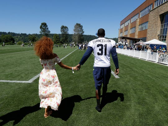 Seahawks safety Kam Chancellor walks with his wife,
