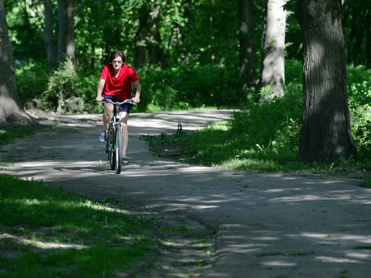 A cyclist winds through trees on the Clive Greenbelt Trail.