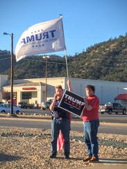 Donning a flag cape and carrying amakeshift sign, two