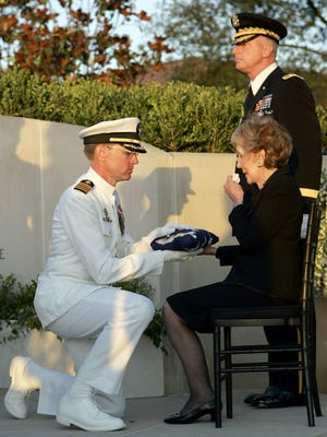 Navy Capt. James A. Symonds, commander of the USS Ronald Reagan, presents the flag to Nancy Reagan during interment ceremonies at the Ronald Reagan Presidential Library in Simi Valley, Calif., on June 11, 2004.